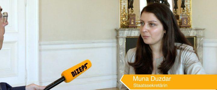Standbild Interview Muna Duzdar. Man sieht rechts Muna Duzdar sitzen auf sie ist von links ein Mikrofon gerichtet mit der Aufschrift BIZEPS