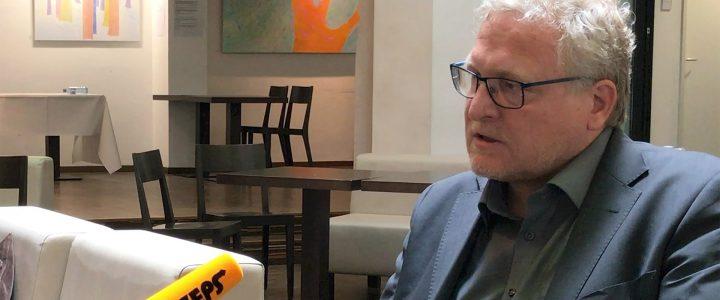 Standbild Interview Albert Brandstätter. Man sieht rechts Albert Brandstätter sitzen auf ihn ist von links ein Mikrofon gerichtet mit der Aufschrift BIZEPS