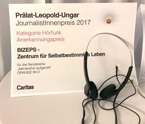Schild mit Aufschrift Prälat-Leopold-Ungar JournalistInnenpreis 2017 Anerkennungspreis Hörfunk BIZEPS für barrierfrei aufgerollt. Davor ist ein Kopfhörer um sich die Sendung anhören zu können.