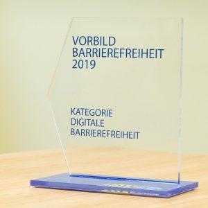 Eine transparente Trophäe mit blauer Bodenplatte, Text: Vorbild Barrierefreiheit 2019 Kategorie Digitale Barrierefreiheit